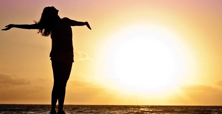 Siluett av kvinne med sol som bakgrunn. Hun er svart, med armene ut, ansiktet vendt oppover, hun sees bakfra.