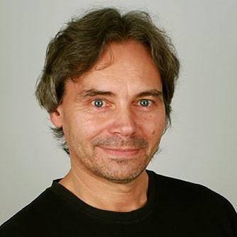 Portrett av mann, i førtiårene, smiler litt, ser mot kamera, brunt hår, har på sort genser.