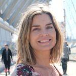 Kvinne smiler mot kamaera, bakgrunn er en moderne bro i Oslo.