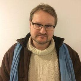 Mann med briller, hvit genser og blått skjerf ser i kamera, står mot beige bakgrunn.