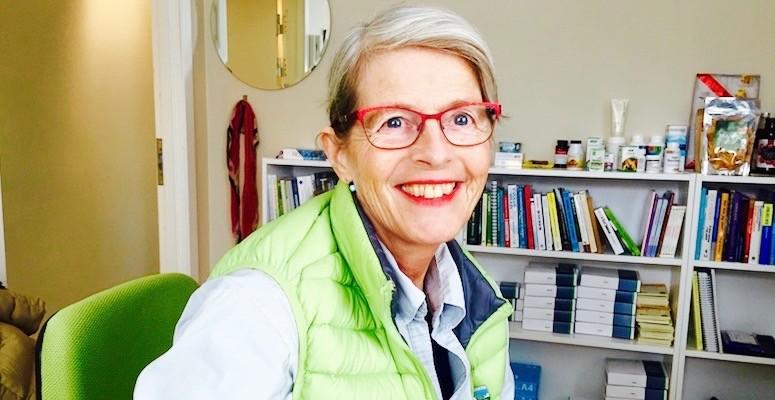 Lege Siri Aabel på sitt kontor. Hun er ikledd en grønn vest, smiler. Bokhyller og bøker i bakgrunnen.