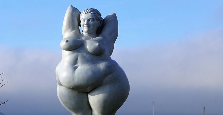 Statue av tjukk dame. Elegant, bakgrunn av himmel og natur.