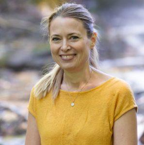 Kvinne ser i kamera, smiler, hun har håret bakover i hestehale. Iført gul t-skjorte. Nøytral bakgrunn.