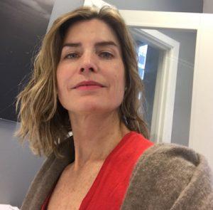 Kvinne ser mot kamera, smiler litt. Hun har på seg rød t-skjorte, omgivelsene er kontor.