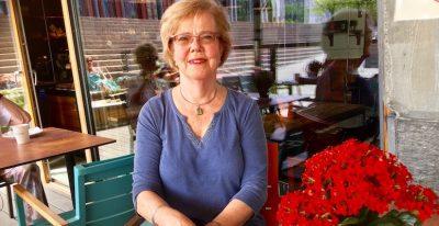 Kvinne sitter ute, med en rød blomst ved sin side. Hun smiler, omgivelsene er utekafe.