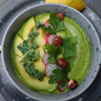Skål med grønn smoothie. Pyntet med rødbeter, avokado, hasselnøtter og persille.