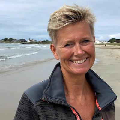 Kvinne med lyst, kort hår smiler mot kamera. Portrett. Hun står på en strand, sjø og bølger i bakgrunnen.
