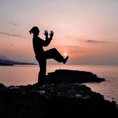 Kvinne i tai-chi positur, tatt i solnedgang, hav og klipper som bakgrunn.