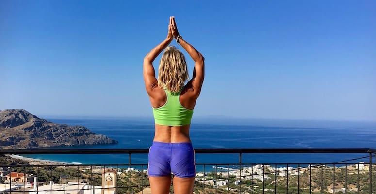 Kvinne i treningsklær med ryggen til. Hun har armene over hodet i yoga-posisjon, hav, fjell og himmel som bakgrunn.