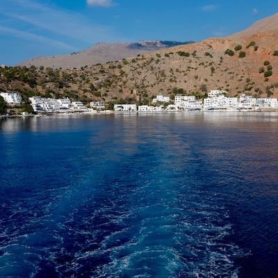 Bilde tatt fra båt, viser hav med hvite hus i bakgrunnen, stedet Loutro på Kreta. Også bakgrunn av fjell og himmel.