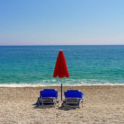 Rød parasoll og blå solstoler på strand. Blått hav og himmel som bakgrunn.
