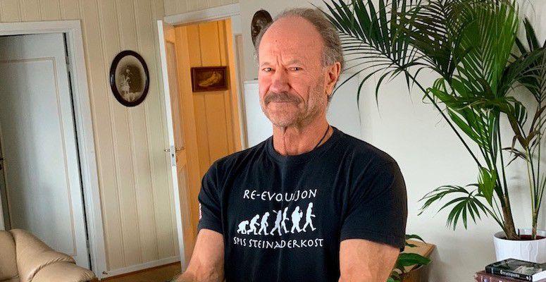 Mann rundt 70 år, ser i kamaera, smiler litt. Iført sort t-skjorte, avbildet i en stue med hvite vegger.