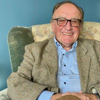Eldre mann sitter i lenestol, briller, hviler hendene i fanget. Smiler, blå vegg bak lenestolen.