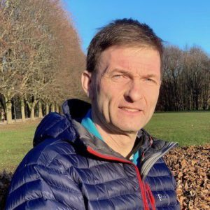 Iver Mysterud, biolog og forfatter. Bakgrunn med trær, gress og blå himmel.