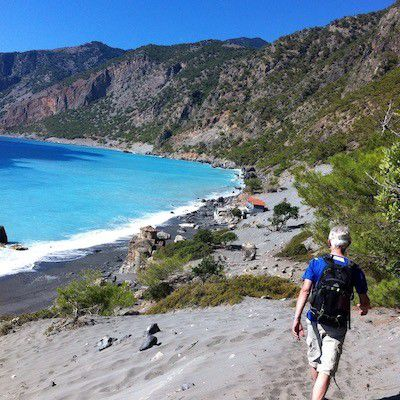 Mann vandrer i sand langs kyst. Miljøet rundt er pinjeskog, fjell, himmel og hav.