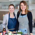 To kvinner med forkle, tatt i kjøkken, ingredienser til mat foran dem på bord.