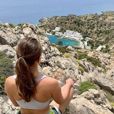 Kvinne med ryggen mot kamera ser utover bukt, Loutro. Miljø av klipper, hav og himmel.