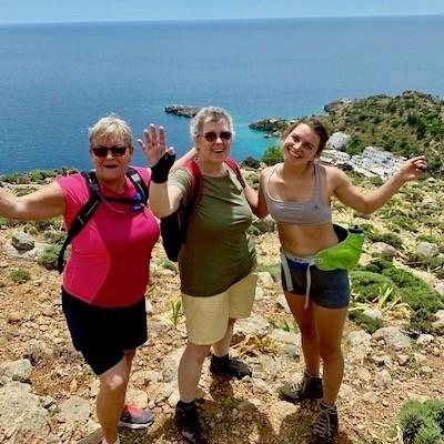 Tre kvinner på tur, smiler mot kamera, hav, himmel og det lille stedet Loutro på Kreta i bakgrunnen.