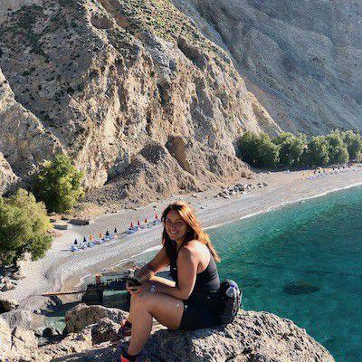 Kvinne sitter på klippe med fjell, strand og turkist hav i bakgrunnen.