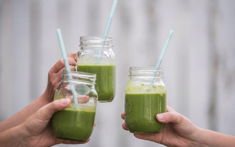 Tre glass med grønn smoothie, holdt av tre hender som skåler. Grå bakgrunn.