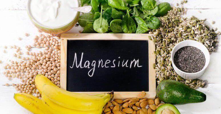 Sort tavle med hvit skrift, magnesium. Omsluttet av bananer, mandler, urter og korn, som er kilder til magnesium.