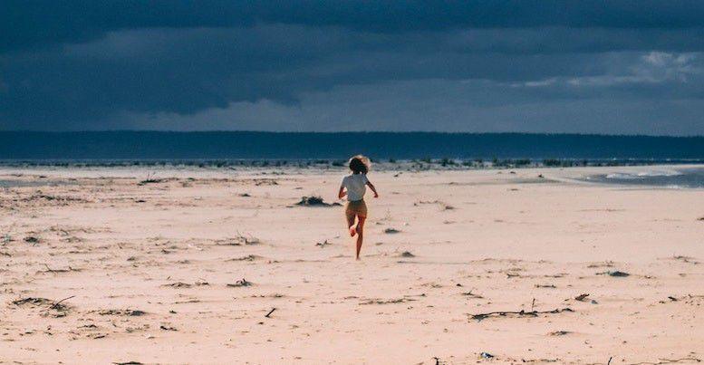 Dame løper på strand med ryggen mot kameraet. Bakgrunn av blå himmel og hav.