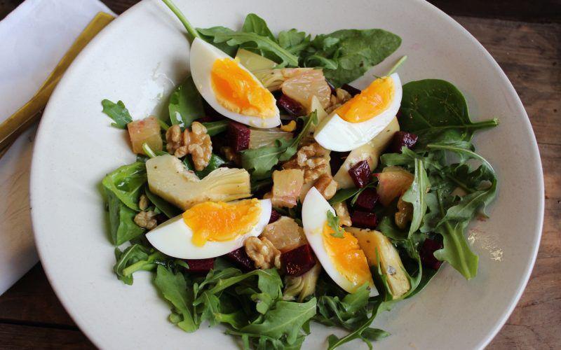 Nærbilde av salat på hvit tallerken: grønne blader, artisjokk, egg og valnøtter.