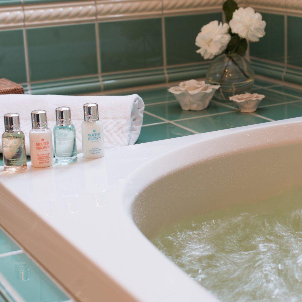 Badekar med vann og bobler, delikat med skjønnhetsprodukter og blomster.