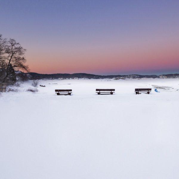 Vinterstemning på Tjøme. Snø og rosa himmel, benker.