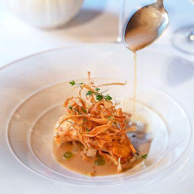 Hvit tallerken, kulinarisk mat, teskje med rennende saus.