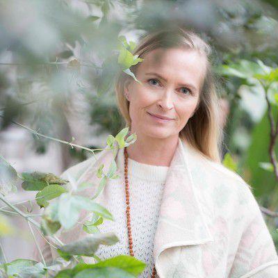 Gry Hammer er blogger og forfatter. Foto tatt ute, trær i bakgrunnen, hun har hvite klær.