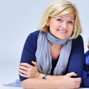 Dame med lyst hår og blå genser, blått skjerf. Ligger på gulvet, hendene rundt albuene, smiler til kamera. Foto tatt i studio.