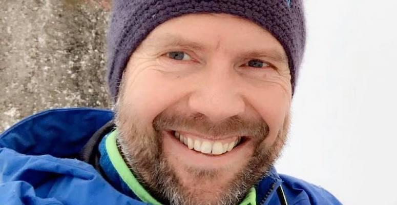Mann som smiler, lue på hodet, ser i kamera, blå jakke.