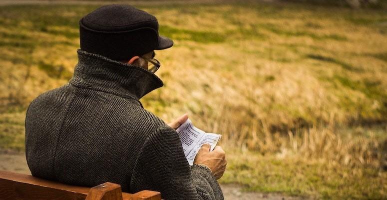 eldre mann sitter på en benk, ryggen mot kamera. Han har hatt, leser i et papir, gress i bakgrunnen.
