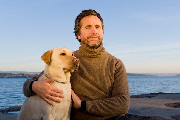 Blind mann ser mot kamera. Ved sin høyre side sitter en hund inntil ham. Hav i bakrunnen, lyset er aftensol.