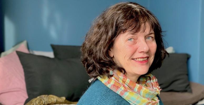 Kvinne med mørkt hår smiler mot kamera. Hun har blå genser, og veggen bak går i samme blåfarge.