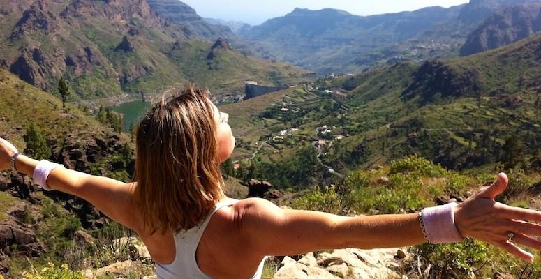 Kvinne ser utover grønn dal, hun har ryggen til, strekker armene ut. Fjell og himmel i bakgrunnen.