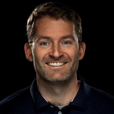 Portrett av mann i trettiårene, han smiler mot kamera, kort brunt hår. Svart, nøytral bakgrunn.