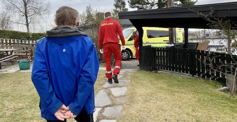 Eldre mann i blå jakke går med ryggen mot kamera. Forhan ham går to ambulansesjåfører kledd i rødt. I bakgrunnen er ambulansen.