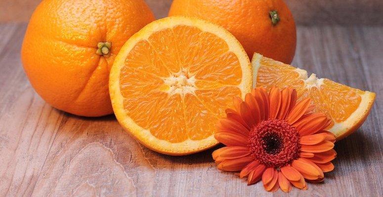 Nærbilde av to hele appelsiner, og en halv, og en oransje blomst. Nøytral bakgrunn.