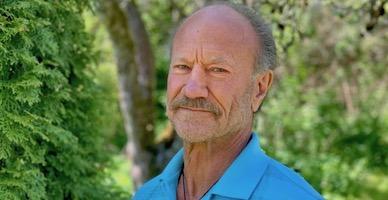 Mann med lite hår og bart ser i kamera, smiler litt. Han har blå t-skjorte på. Bakgrunnen er grønne trær.