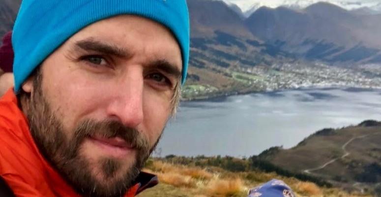 Nært portrett av mann, ser i kamaera. Han har skjegg og blå lue, fjell og fjord i bakgrunnen.