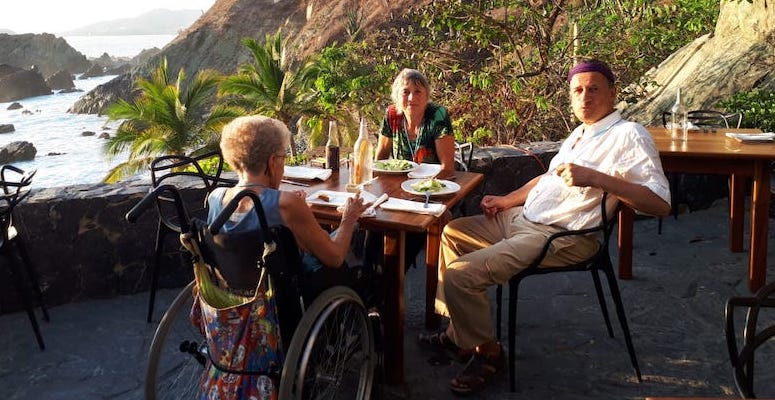 En eldre dame i rullestol, en yngre dame og en mann sitter ute, palmer, sjø og sydlige omgivelser.