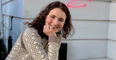 Kvinne med halvlangt, mørket hår hviler haken i hånden, smiler mot kamera. Bak henne er en hvit vegg.