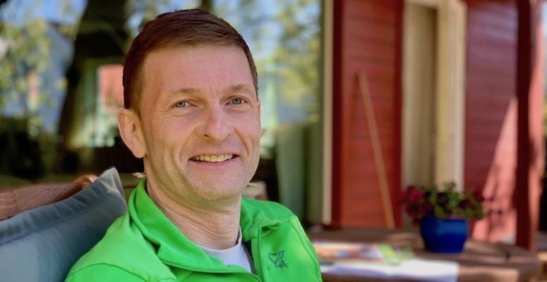 Portrett av mann, han smiler mot kamera, bakgrunn er terasse og utemiljø.